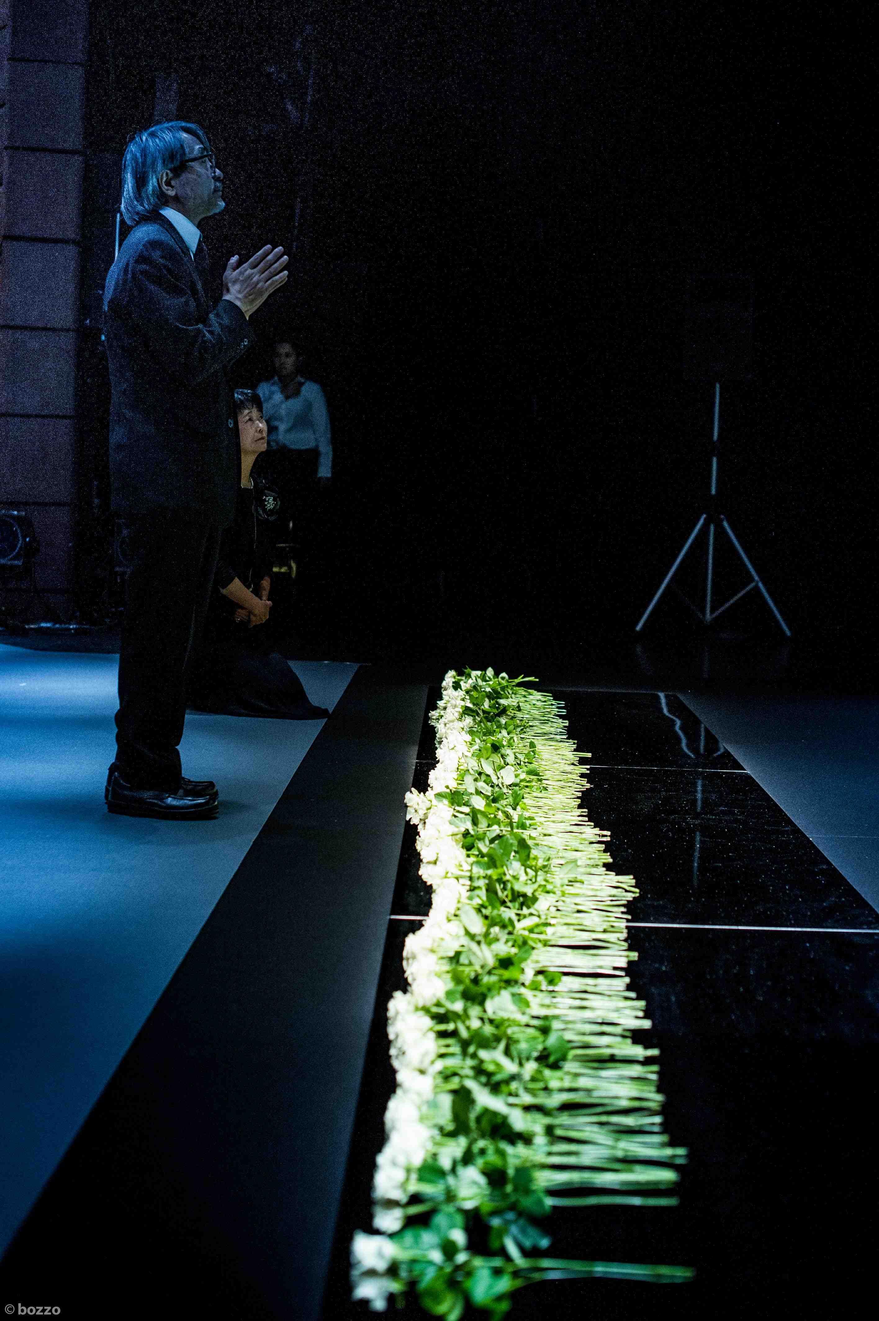 祭壇前の真鍮板の上に献花(手を合わせる司会進行の森下隆さん) ©BOZZO