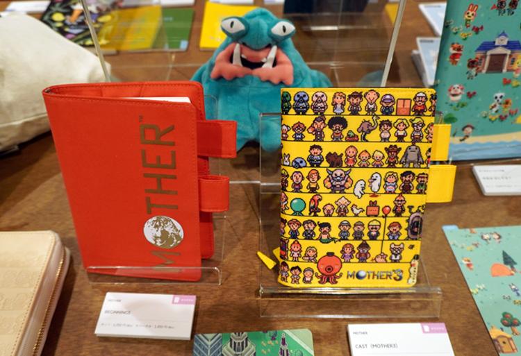 『MOTHER』のファミコンカセットのパッケージとおそろいの赤い手帳と、『MOTHER3』のキャラクターが並ぶひまわり色の手帳。カラフルな色味に、持つだけで元気をもらえそうだ。 (C)SHIGESATO ITOI/Nintendo