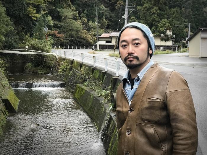 城崎温泉中心部へと流れる、大谿川沿いにたたずむタニノクロウ(庭劇団ペニノ)。 [撮影]吉永美和子