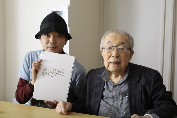 渡辺宙明氏のサインを掲げる高木大地(左)と、渡辺宙明氏本人(右)   (写真提供:モノ・マガジン)