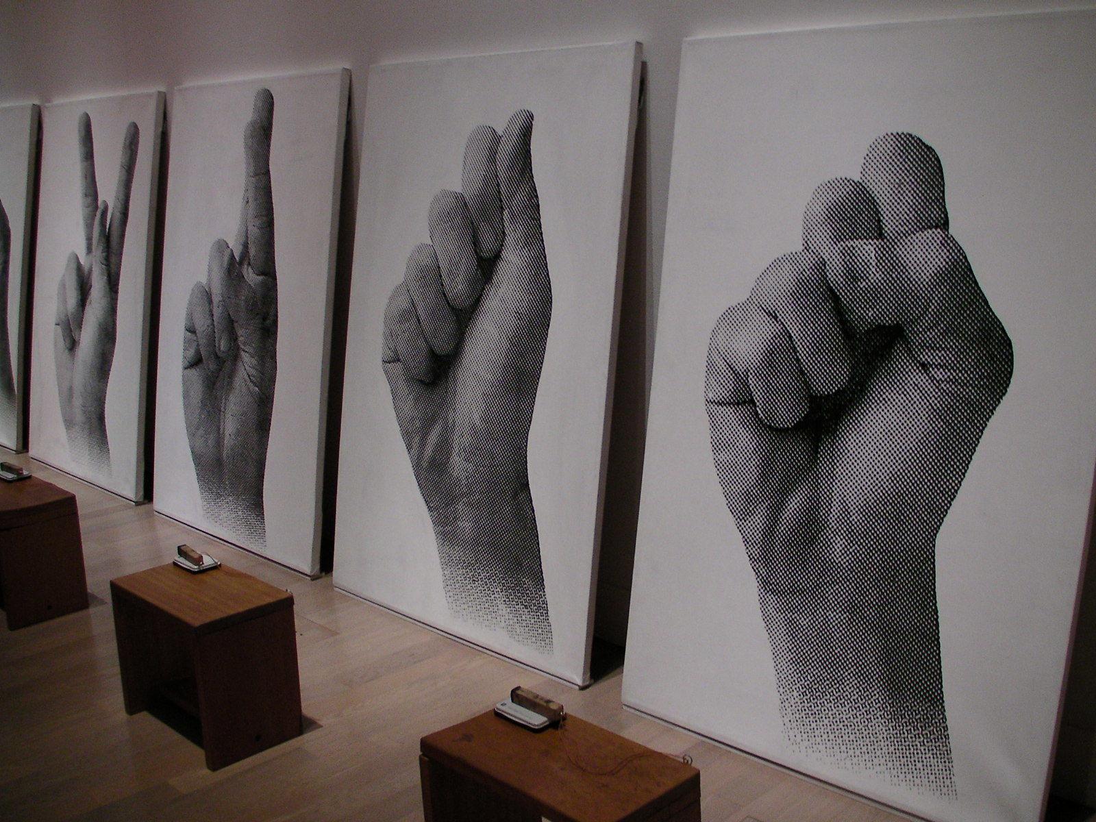 FX ハルソノ《声なき声》1993-94年 パネルの手前には指文字に対応するアルファベットが刻まれたスタンプが置かれ、鑑賞者は自由に紙に押すことができる。