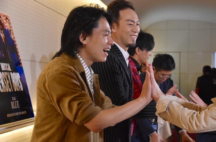 来場者とハイタッチをする中川晃教(手前)と、笑顔で見守る福井晶一
