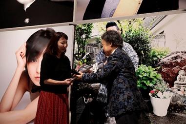 写真左から:100万人記念のお客様・佐藤直美さん、篠山紀信