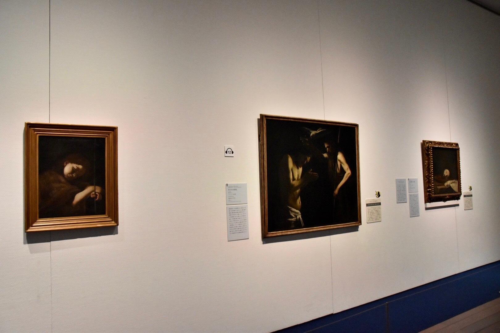 左:バッティステッロ・カラッチョロ(本名ジョヴァン・バッティスタ・カラッチョロ)《子どもの顔あるいは幼い洗礼者聖ヨハネ》1607-10年頃(市立フィランジェリ美術館蔵)、中央:同作者《キリストの洗礼》1610年頃(ジロラミーニ教会絵画館蔵) 右奥:ジュゼペ・デ・リベーラ《洗礼者聖ヨハネの首》1646年(市立フィランジェリ美術館蔵)