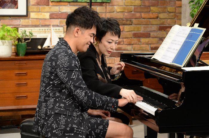 おしゃれな半パンのスーツ姿でピアノに向かう武井。熊本が熱心に指使いを指導する場面も
