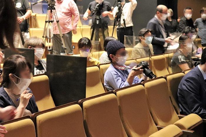 会見に臨む報道陣の様子。座席の間を空けさらに敷居を設けていました。