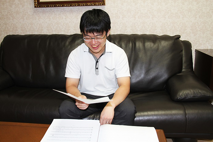 嬉しそうに弦楽器のパート譜を眺める太田弦 (C)h.isojima
