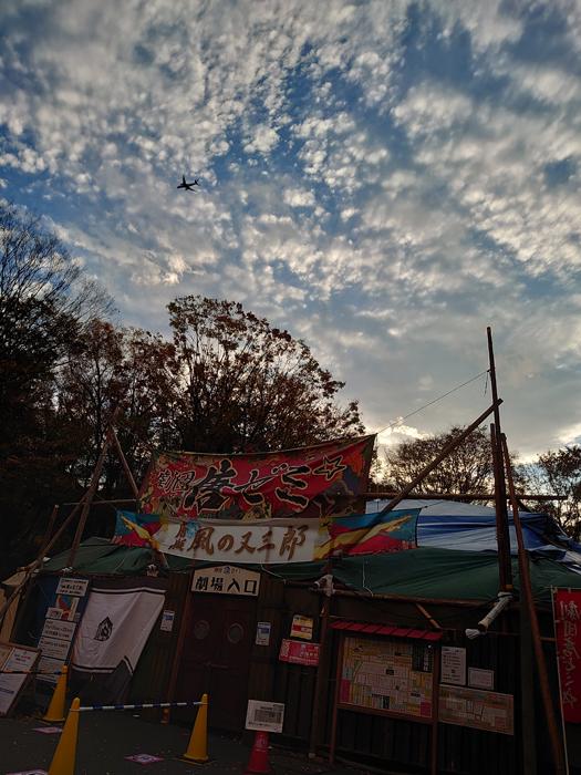 青テントの上空を飛行機がよぎる (写真提供:劇団唐ゼミ☆)