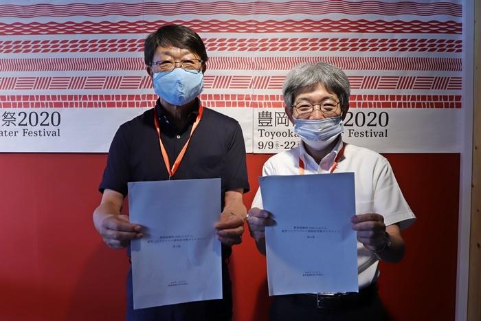 『豊岡演劇祭2020』第二回会見より。「新型コロナウイルス感染症対策ガイドライン」のレジュメを持つ中貝宗治豊岡市長(左)と平田オリザフェスティバルディレクター。