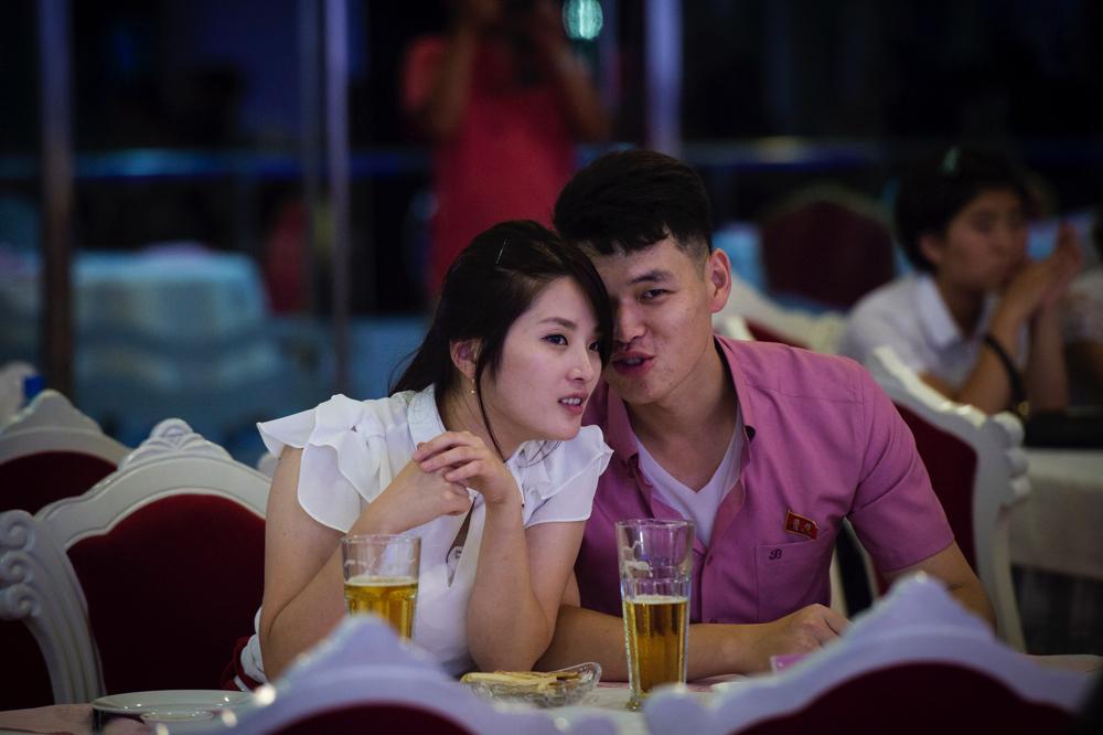 平壌市内のカフェで囁き合う恋人同士。