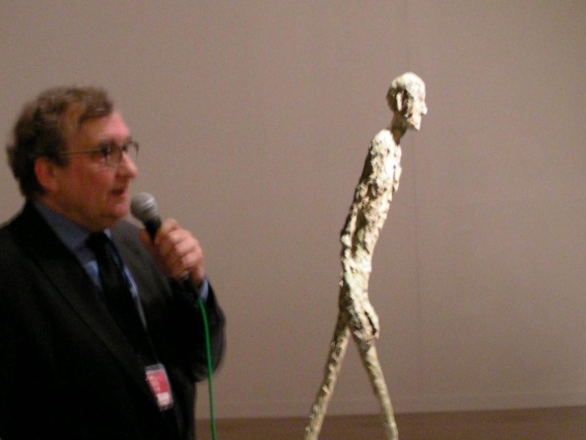 13日に開催された内覧会にて《歩く男》の横で解説をするマーグ財団美術館館長オリヴィエ・キャプラン 「ジャコメッティ作品の魅力は人間の儚さと同時に、それに押しつぶされない強さを持っているところだ」