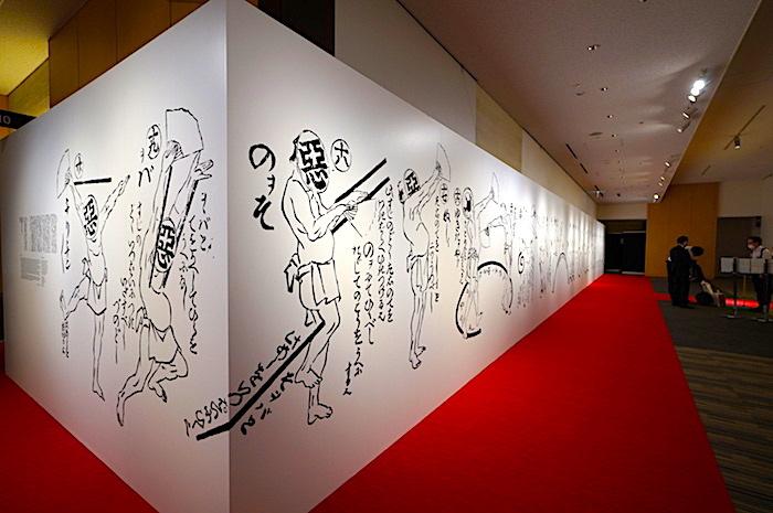 """会場エントランスでは「踊独稽古」の人物がコミカルにお出迎え。これは文化時代に流行していた """"悪玉踊り"""" の振り付けを練習するためのお手本画である"""