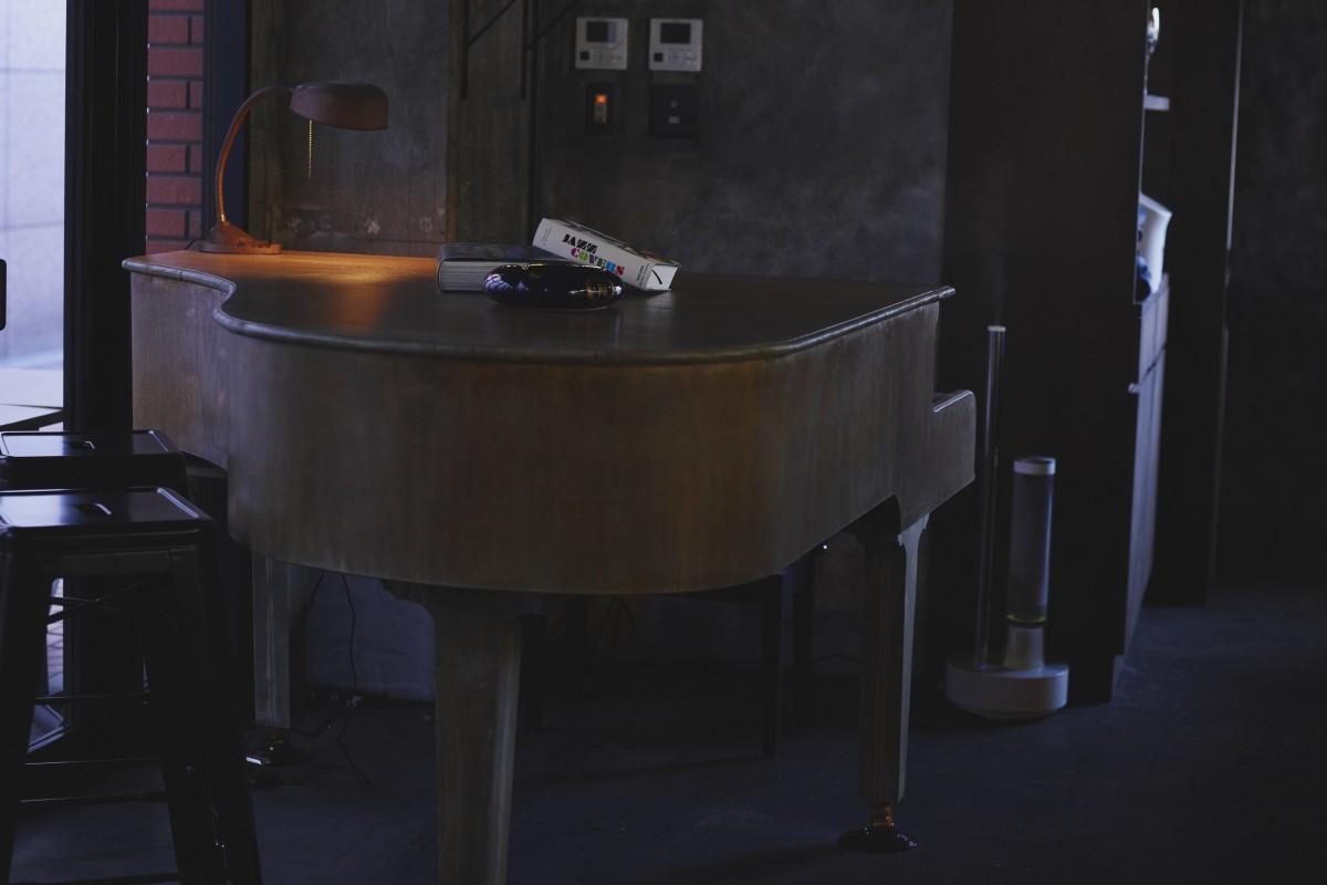 この店のために特別に作られた、グランドピアノを模したテーブル。しかし、なかには電子ピアノが仕込まれていて演奏することもできる。店内の隅々まで遊び心が効いていた空間だ。