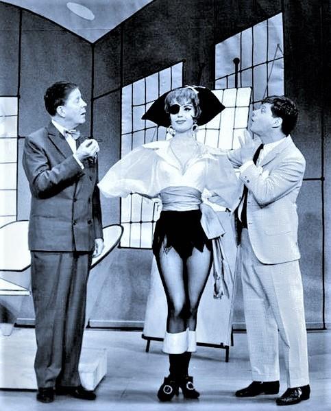 『ハウ・トゥー・サクシード』ブロードウェイ初演(1961年)の舞台より、右端が主人公フィンチ役のロバート・モース。左端がルディ・ヴァリー(ビグリー社長)。ヴァリーは往年の人気歌手だった。