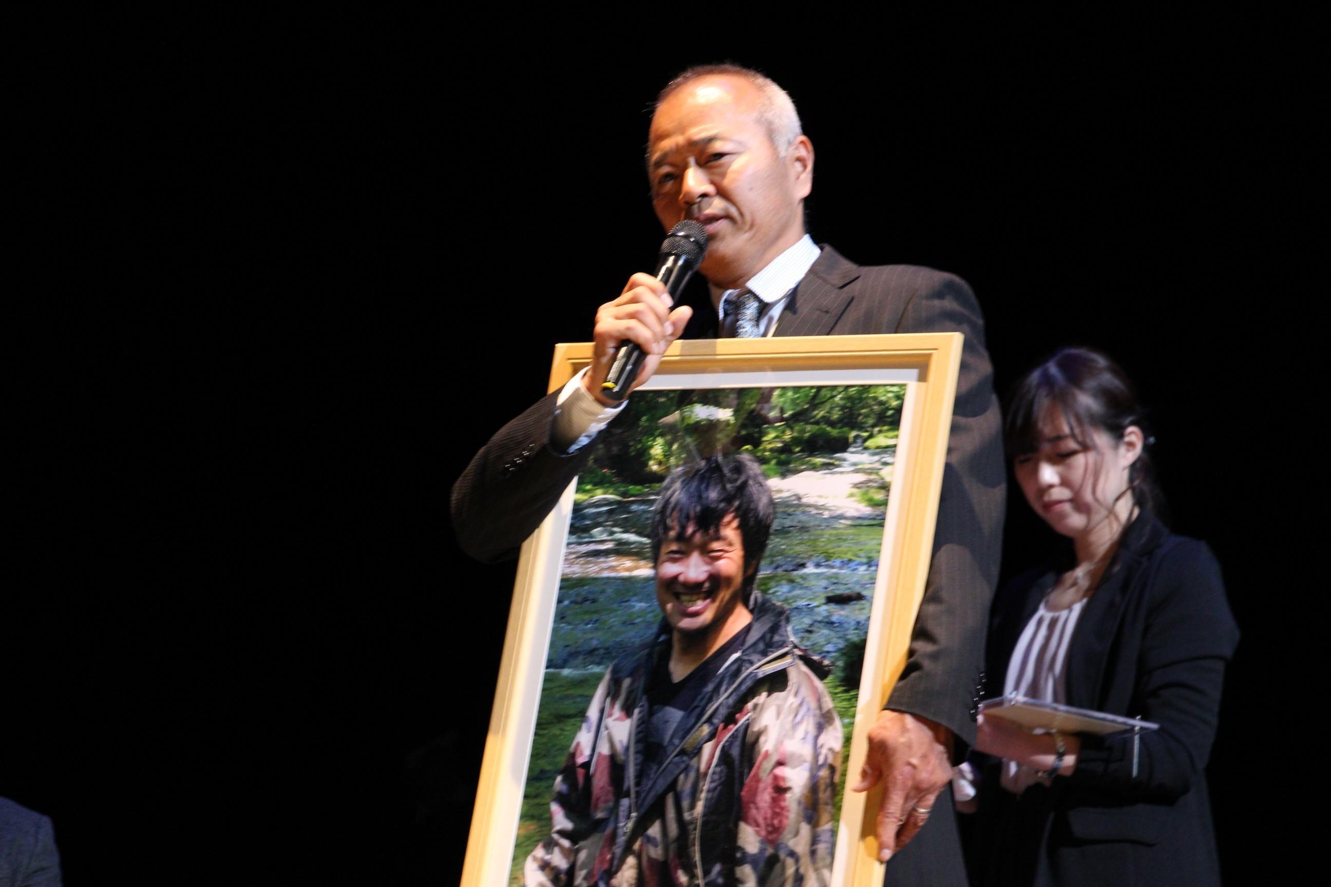 左から、舟山弘一さんの写真を掲げる辻井啓伺氏、舟山さんの妻・めぐみさん