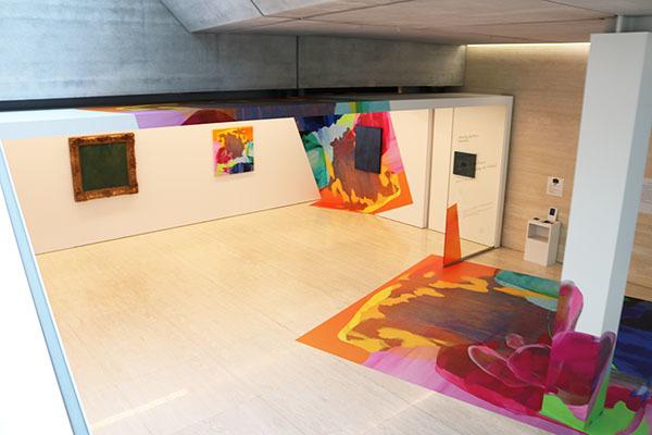 『流 麻二果 ―色を追う/Tracing the Colors』展示風景。エスカレーターを下るところから既に展示は始まっている。