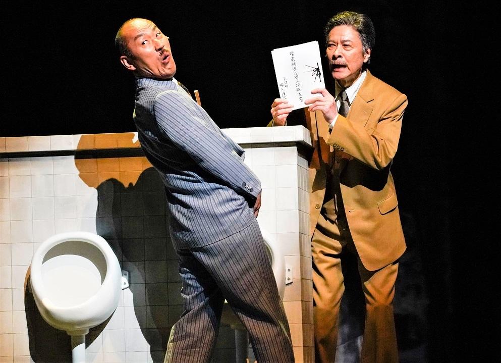 助役に扮する山西惇(左)と鹿賀 ©引地信彦