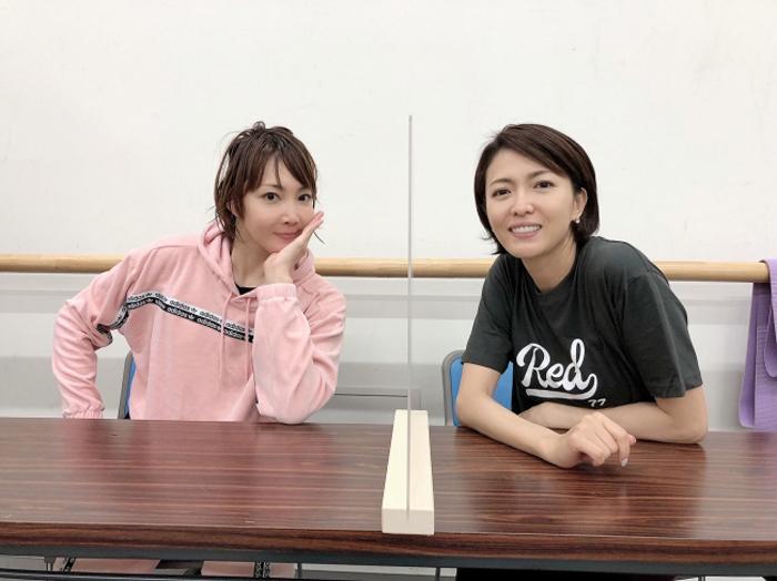 柚希と、新キャストで同役を演じる安蘭けい(右)。机には仕切りが設置されている ©ホリプロ