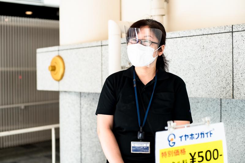 株式会イヤホンガイド 広報担当の小峯さん。フェイスシールド、マスク、手袋を着用して接客する。