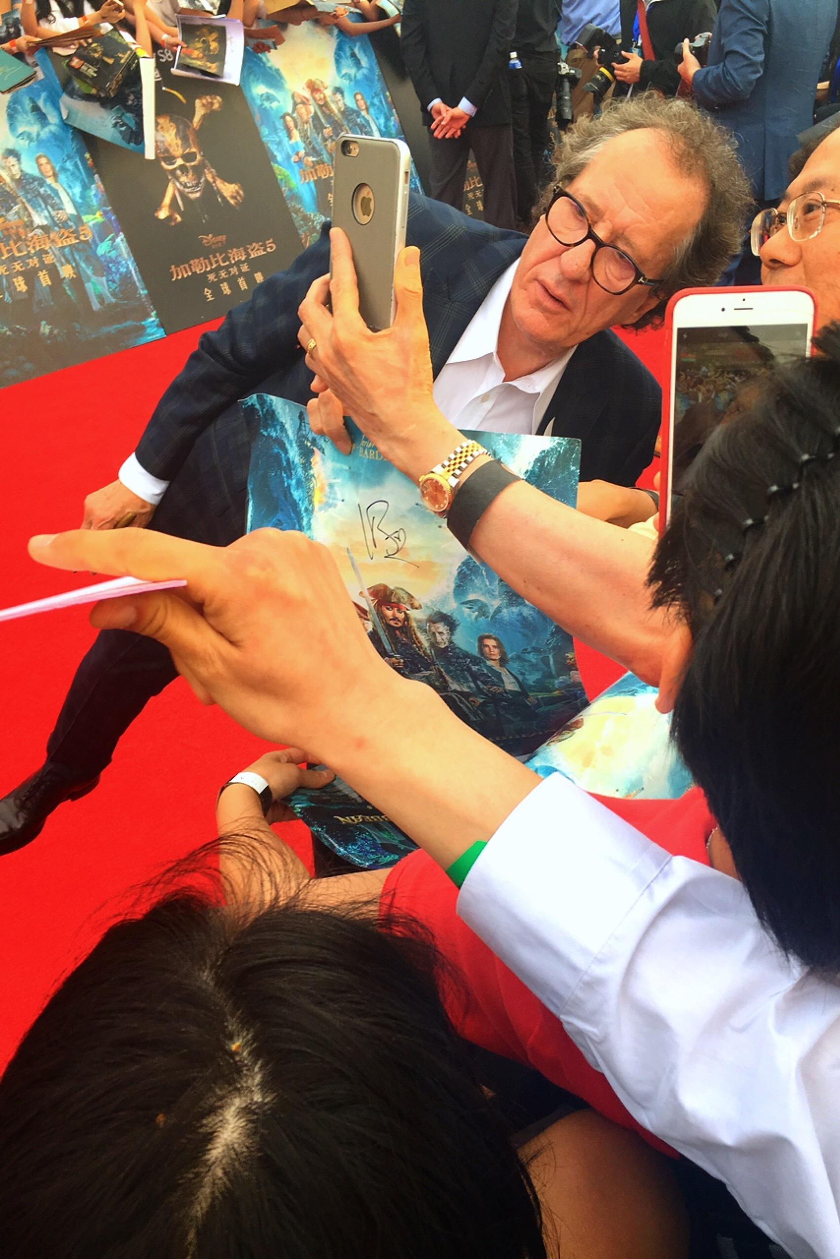 軽やかな足取りでファンのセルフィーにおさまるジェフリー・ラッシュ 撮影=村田 由美子