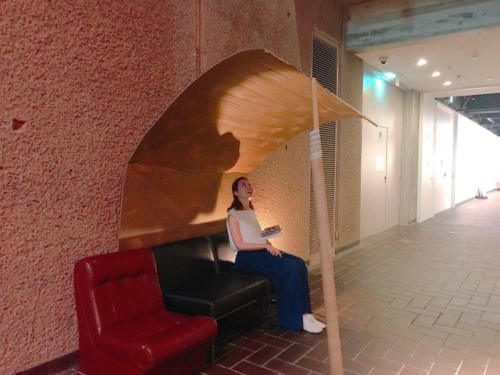 吹き抜けの展示室に抜ける途中には、本展準備を手伝った東京藝術大学の学生が日頃使っているソファと、この空間に合わせてつくった屋根が。
