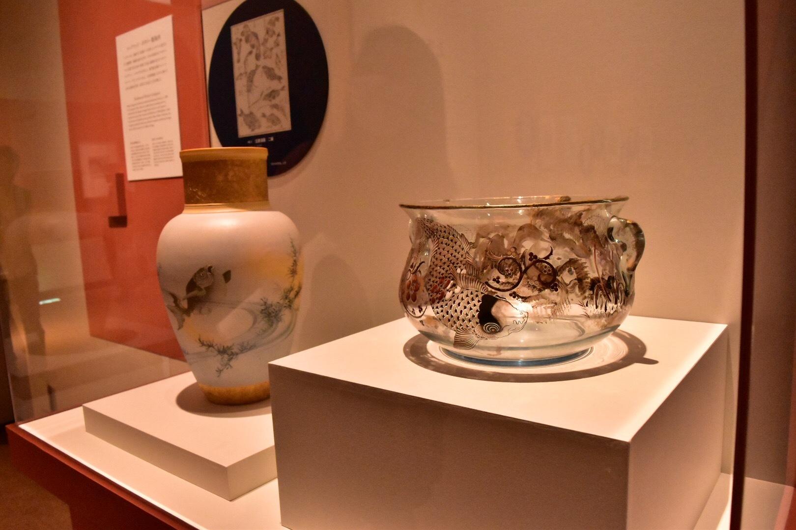 右:エミール・ガレ《双耳鉢:鯉》1878-90年 個人蔵  左奥:アルバート・ロバート・ヴァレンタイン(絵付)ルックウッド・ポタリー製陶所《花器:金魚》1885年 シンシナティ美術館