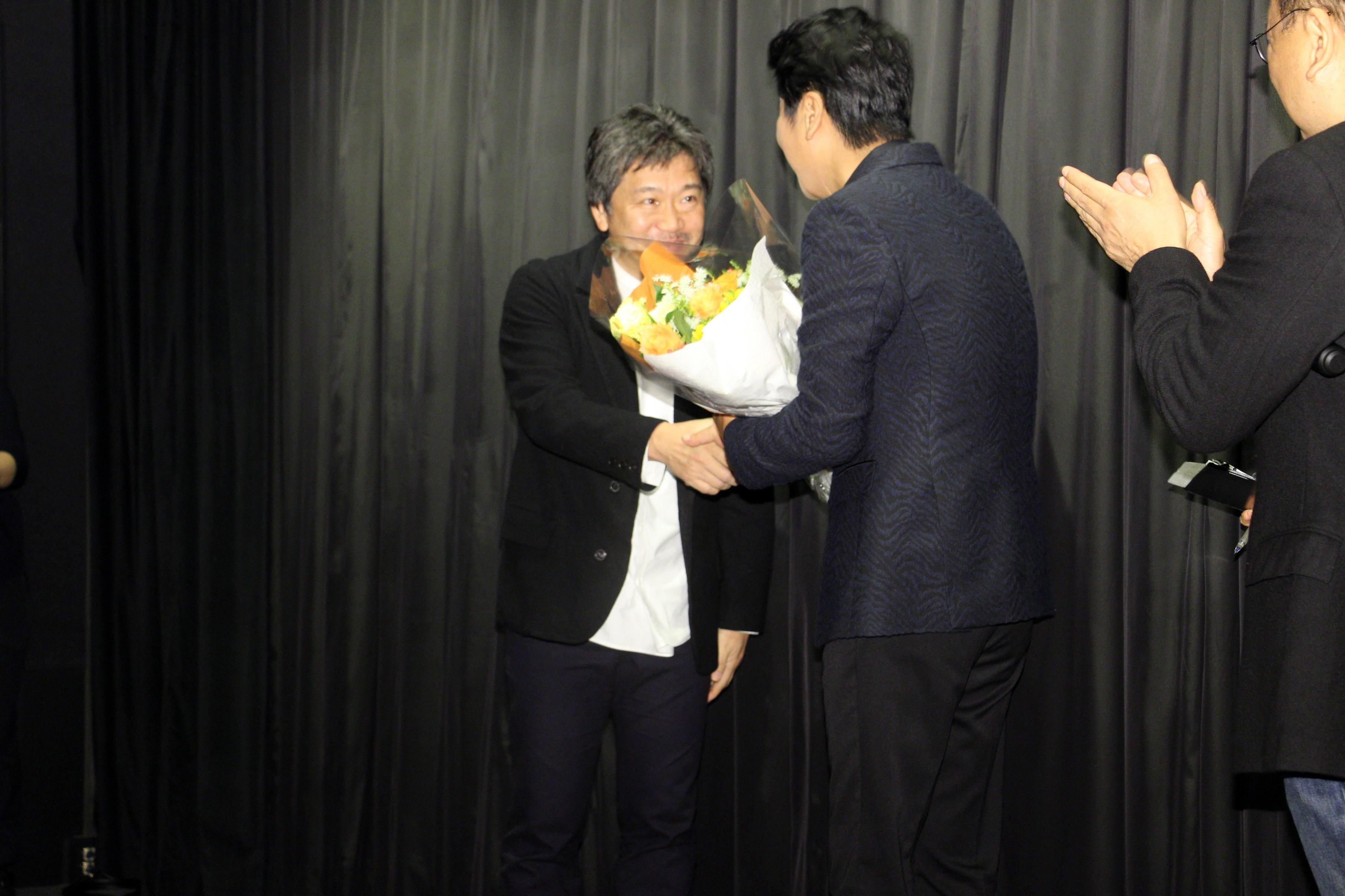 ソン・ガンホに花束を渡す是枝裕和監督