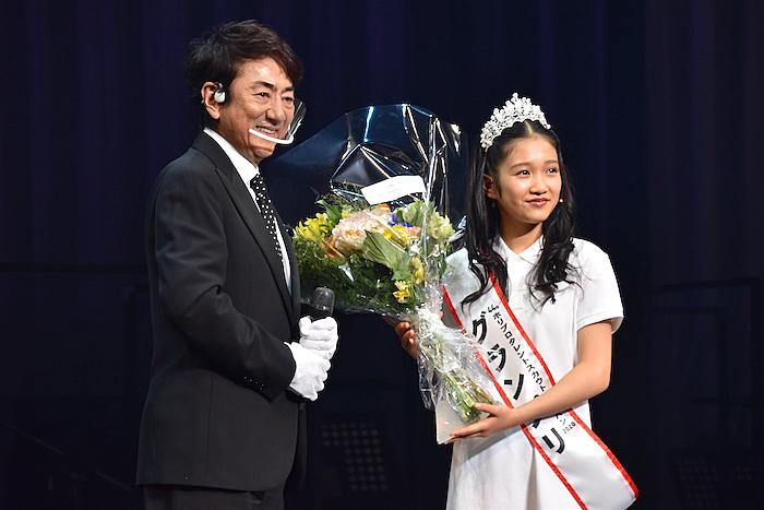 花束を受け取る山﨑玲奈さん(右)と、スペシャルアンバサダーの市村正親  (撮影:五月女菜穂)