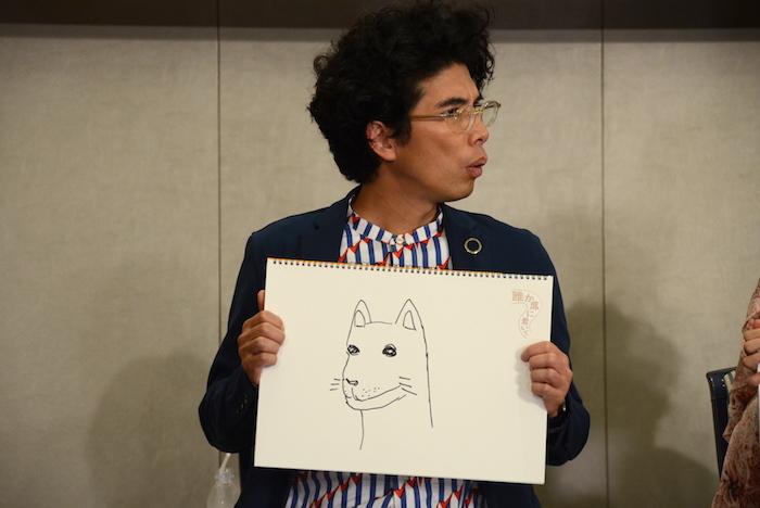 自分で描いた絵を持つ片桐仁