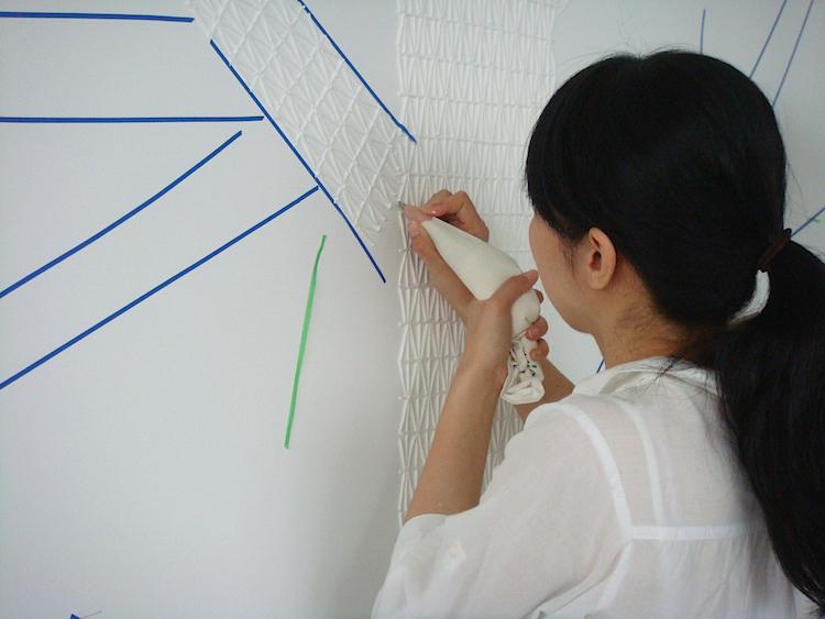 制作の様子。石膏ボードにマスキングテープを貼って描く位置を決め、延々と模様を描いていくという、実に根気のいる作業