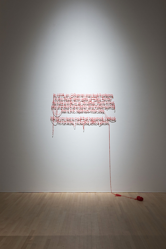 ミヤギフトシ《1970》1970年/作家蔵  赤い毛糸とピンを使って、壁に英文のテキストが綴られている