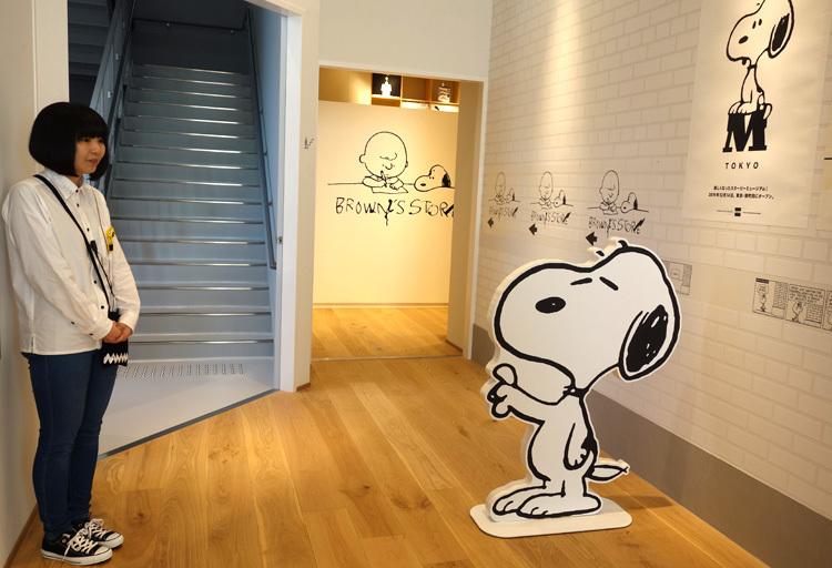 手前はミュージアムの中へと案内するスヌーピー。奥に見えるのはたくさんのグッズが取り揃えられた「ブラウンズストア」。 (C) Peanuts Worldwide LLC