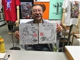 サイン色紙を持った開田裕治氏
