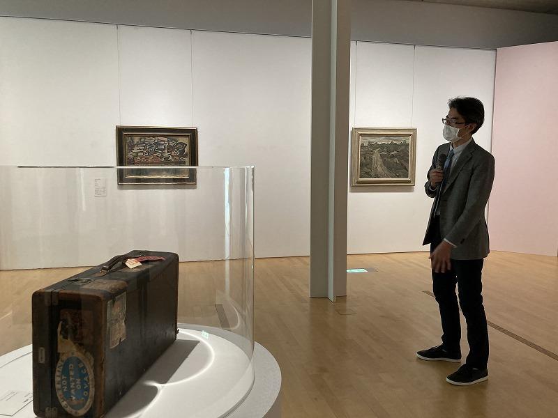 フジタ展を担当した内呂博之学芸員と、フジタが愛用した遺品のトランク