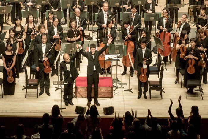 感動のお披露目でスタンディングオベーションに応える。指揮者の広上と岸田(最前列) 昨年12月、ロームシアター京都メインホールで。pics by 井上嘉和
