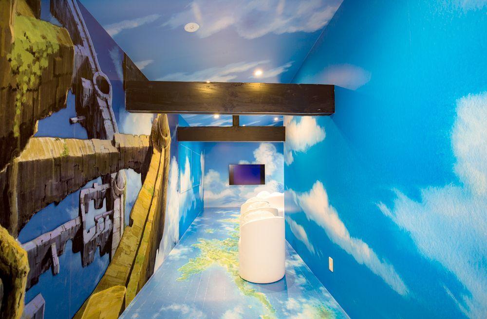 空と雲の部屋。山本二三氏が描いた空と雲で囲まれている。雲のソファで短編アニメを見ることができ、このコーナーでは写真撮影が可能になっている