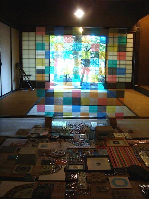 畳の上に並べられた装飾タイルとカラフルなガラス越しに庭の景色を望む、田島秀彦の《窓から風景へ》