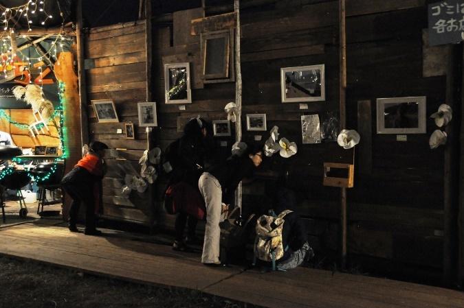 板の隙間から公演の様子をうかがう人々。壁には様々な年代の松本雄吉の写真が展示されていた。 [撮影]吉永美和子