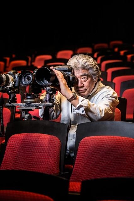 舞台で写真を撮影中の谷古宇正彦氏。両目を開いたまま、被写体を狙う。 撮影/Shinichiro Saigo