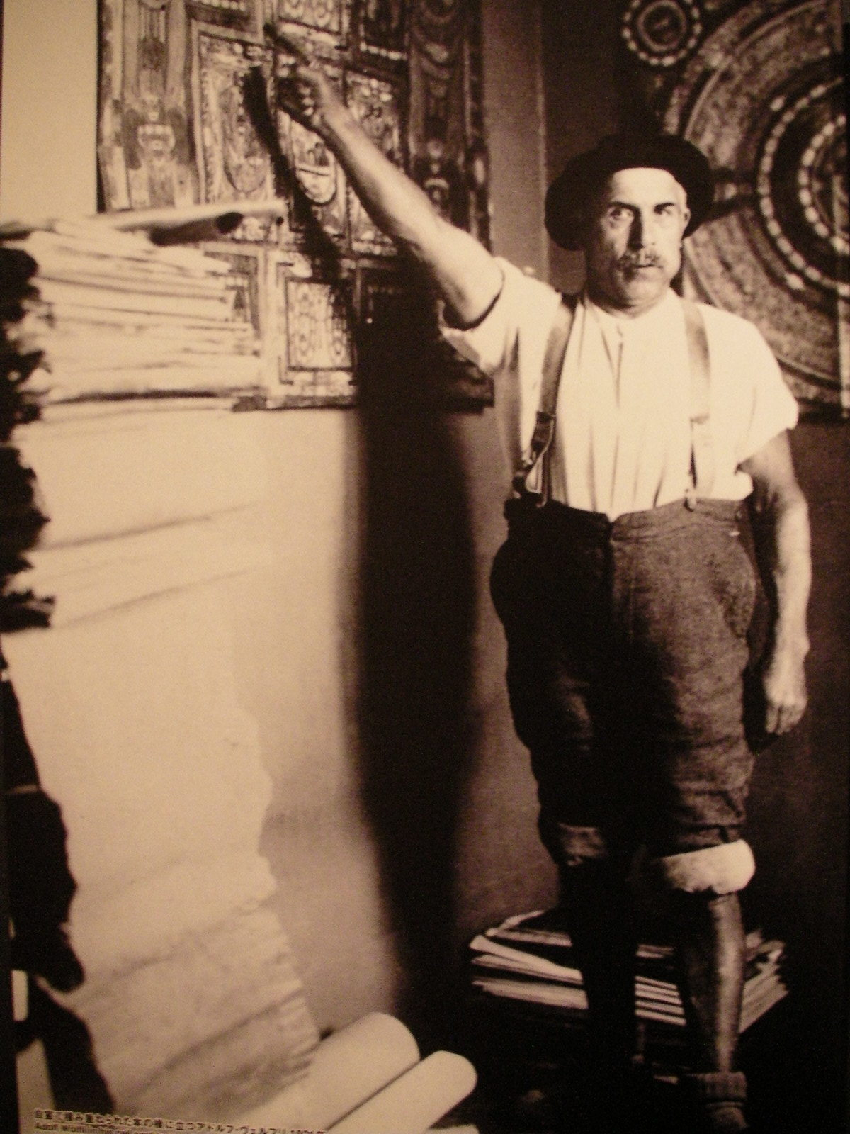 自室で積み重ねられた本の横に立つアドルフ・ヴェルフリ(1921)