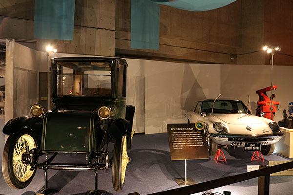 左:Milburn(ミルバーン)電気自動車 1920(大正9)年ごろ、国立科学博物館所蔵  右:マツダ コスモスポーツ 1967(昭和42)年、国立科学博物館所蔵