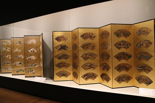 右は《源平合戦扇面貼交屛風》江戸時代(個人蔵)、左は《北野天神縁起絵扇面貼付屛風》室町時代 16世紀(大阪・道明寺天満宮所蔵》(ともに全期間展示、ただし場面替あり)