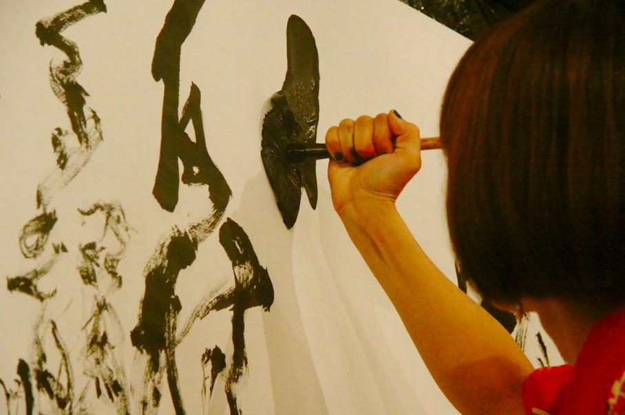 時には筆をグーの手で握り、力強く描く場面も