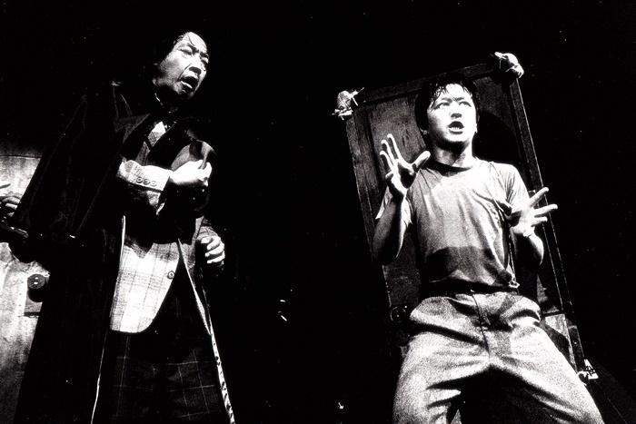 唐組『ジャガーの眼』(95年再演)。当時の辻孝彦(右)は「扉を背負っている男」を演じた。 ©唐組