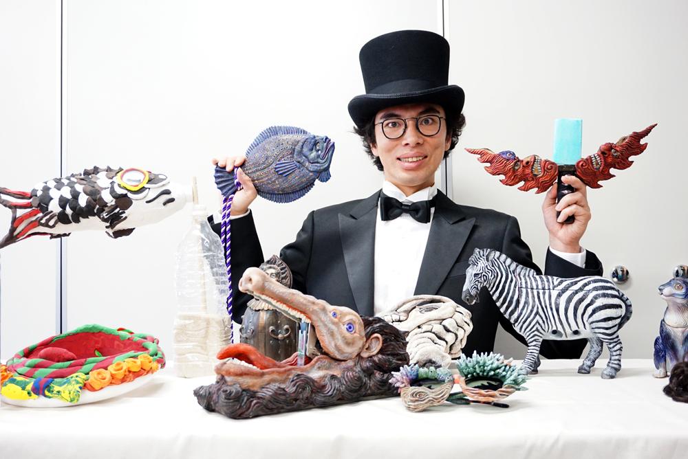 『ギリ展』に出品する作品に囲まれ、作品解説する片桐仁