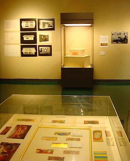 手前は正義が手がけた劇場の緞帳デザイン。奥は正義考案の建築プラン《完全機能構造体(FFC住宅)模型》。太郎唯一の建築「マミ会館」の模型や、日用品デザインも展示されている