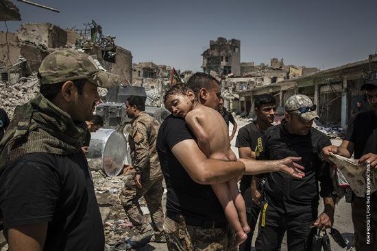 世界報道写真コンテスト 一般ニュースの部 組写真1位 イヴォール・プリケット(アイルランド) ニューヨークタイムズに提供、 2017年7月12日 モスルをめぐる戦闘:イラク軍特殊部隊の兵士によって手当てをうける身元不明の男の子。