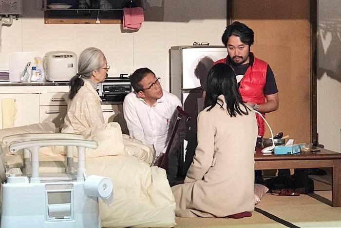タニノの説明を聞く『笑顔の砦』介護家族チーム。(左から)百元夏繪、たなべ勝也、坂井初音。