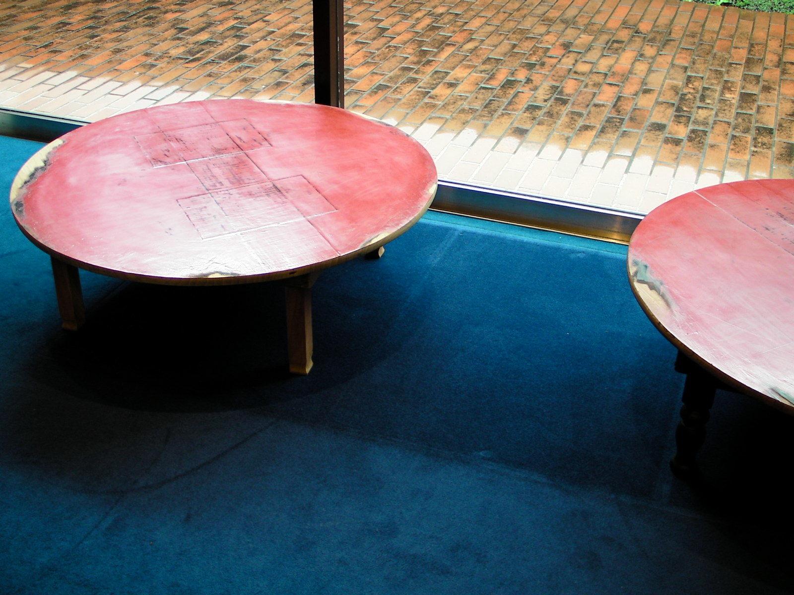建築家の長坂常による作品。アンティークのちゃぶ台を、あえて素材感や制作過程が読みとれる状態で会津塗りを施した。ロイヤルブルーの絨毯が印象的な「カラー」の店内に展示。 [map:25] @kolor