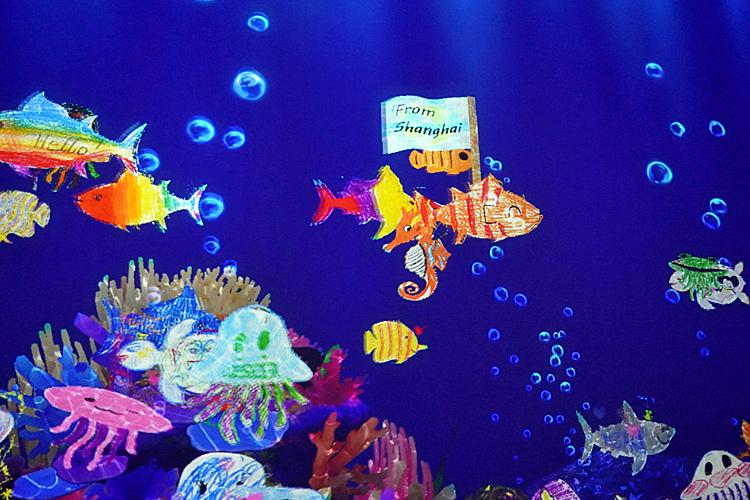 《世界とつながったお絵かき水族館》。「from shanghai」と書かれた旗を持つマグロがいる。